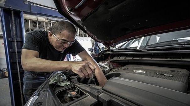 Un homme répare une voiture